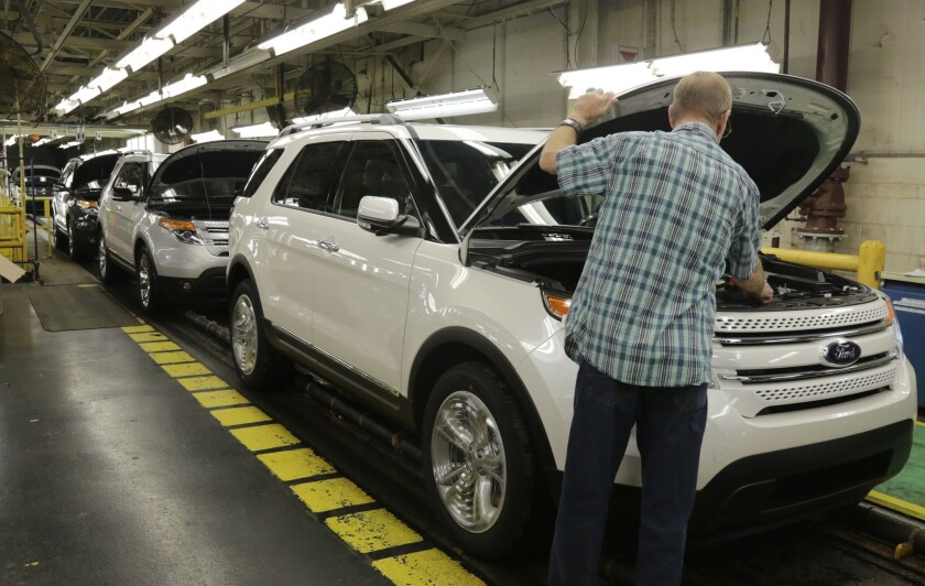 Workers perform final inspections on 2015 Ford Explorers on the assembly line at the Chicago Ford Assembly Plant on Wednesday.
