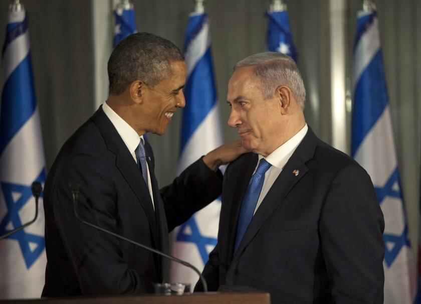President Barack Obama, left, pats the shoulder of Israeli Prime Minister Benjamin Netanyahu during a joint news conference in Jerusalem, Israel.