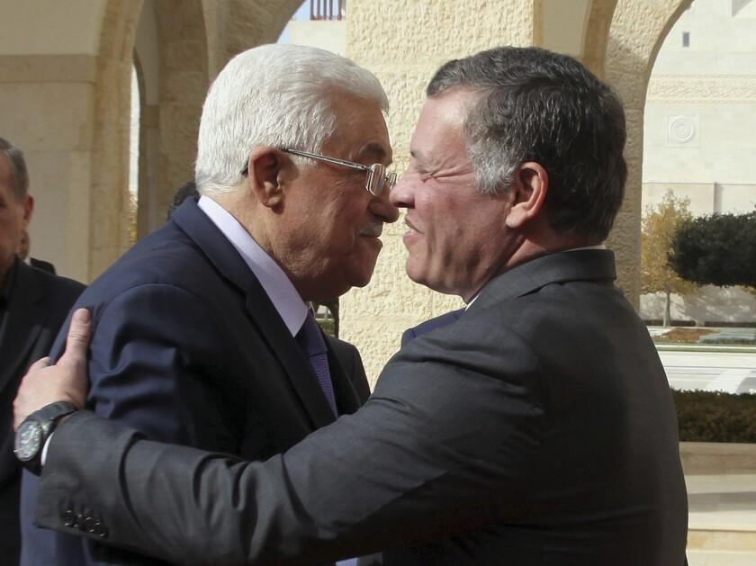 Jordan's King Abdullah II, right, welcomes Palestinian Authority President Mahmoud Abbas at the Royal Palace in Amman, Jordan.