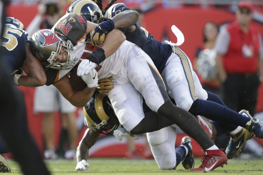 Rams defenders tackle Buccaneers tight end Cameron Brate during third quarter action at Raymond James Stadium.