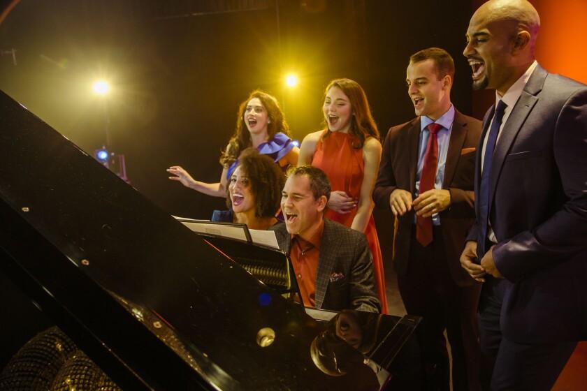 Lesli Margherita, Andrea Ross, Ryan Vona, Nicholas Christopher, Ashley Blanchet and Andy Einhorn sing around a piano.