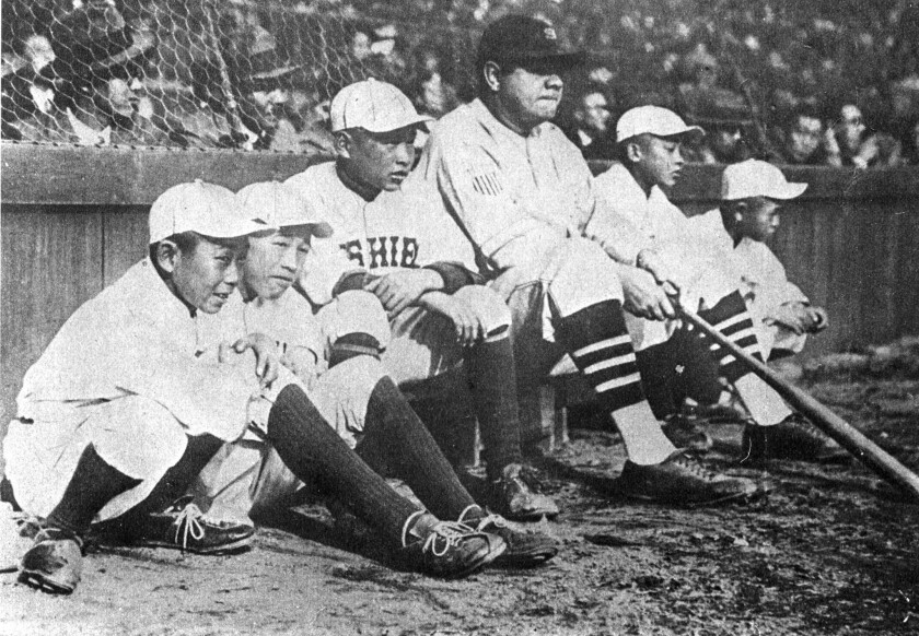During a 1934 tour of Japan, Babe Ruth poses on a Tokyo field for a photo with young Japanese players.
