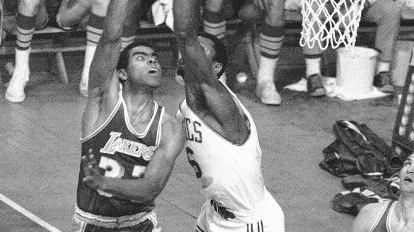 Lakers' Tommy Hawkins shoots over Boston Celtics' Bill Russell in the fourth quarter during a game o