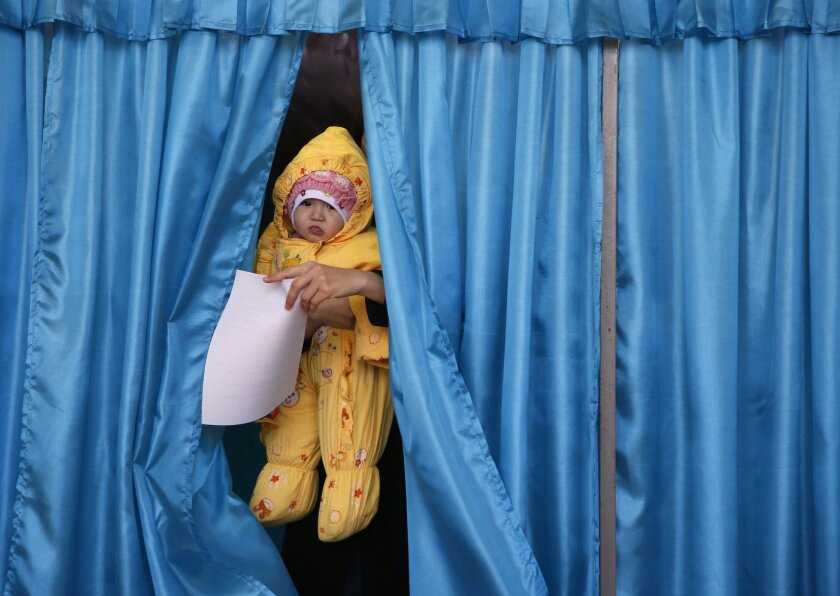 A baby held by a voter comes out from a voting cabin at a polling station during Kazakhstan parliamentary elections at the Russian-leased Baikonur Cosmodrome, Kazakhstan, Sunday, March 20, 2016. (AP Photo/Dmitri Lovetsky)