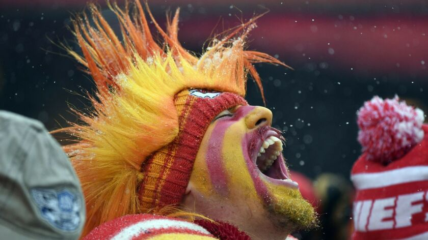 A Kansas City Chiefs fan yells in the stands during the first half of an NFL divisional football pla
