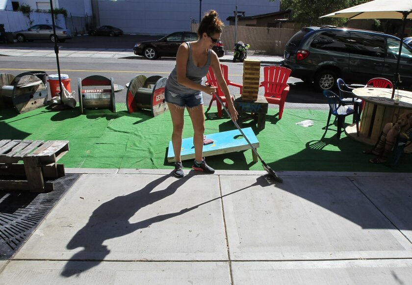 Heidi Arni sweeps her parking space -- turned temporary parklet -- at 15th and Market streets on Park(ing) Day.