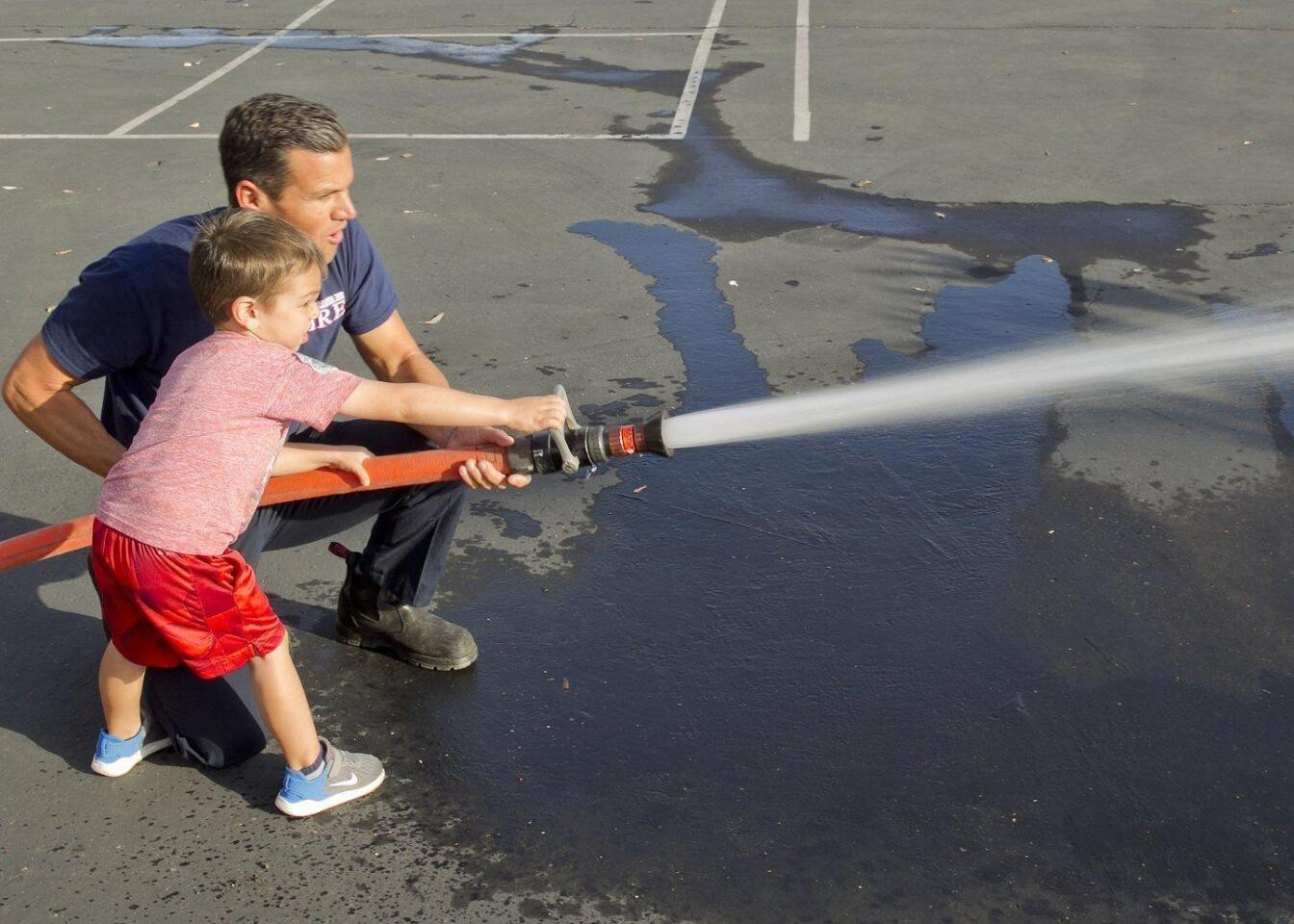 Firefighter Tim Wood helps Liam Clapper use the fire hose