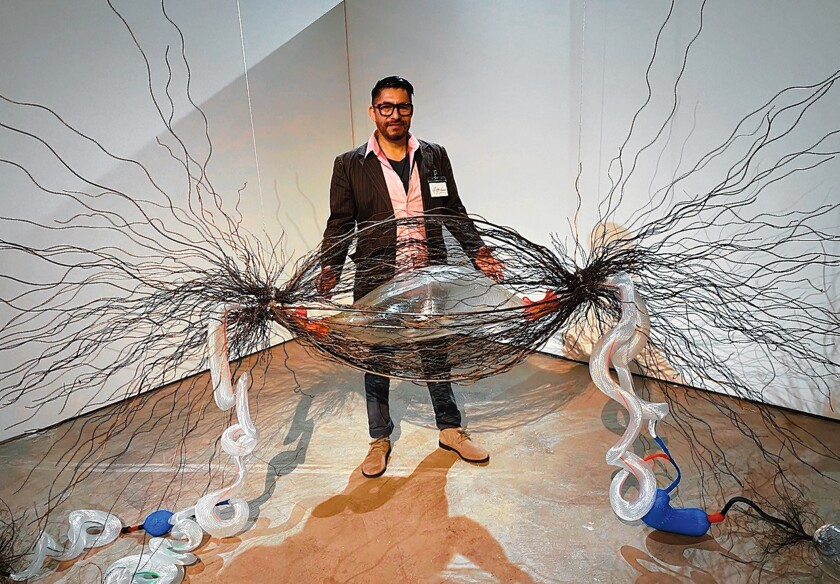 Glass artist Hugo Heredia Barrera, with his supersized cancer-infected cell, trapped in steel threads and connected by plastic DNA tubes to some still-healthy, clear-glass cells. 'Illumination: 21st century interactions with art, science and technology' is on exhibit through May 3, 2020 at San Diego Art Institute, 1439 El Prado in Balboa Park, San Diego. Hours: noon to 5 p.m. Tuesday-Sunday. (619) 236-0011. sandiego-art.org