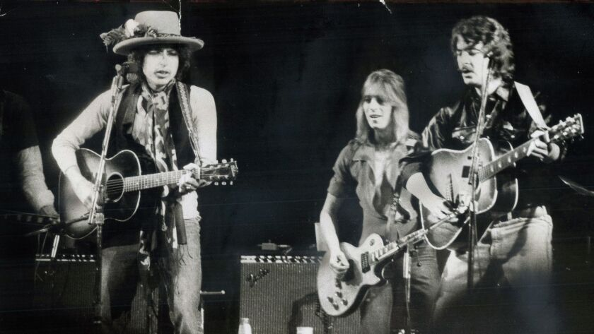 Bob Dylan, left, Mick Ronson and Bobby Neuwirth perform in Dylan's Rolling Thunder Revue tour in 1975.