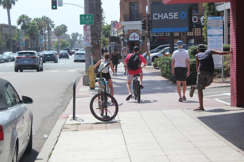 Bicyclists pedal along on the sidewalk rather than risk their necks by driving in traffic on Garnet Avenue in Pacific Beach.