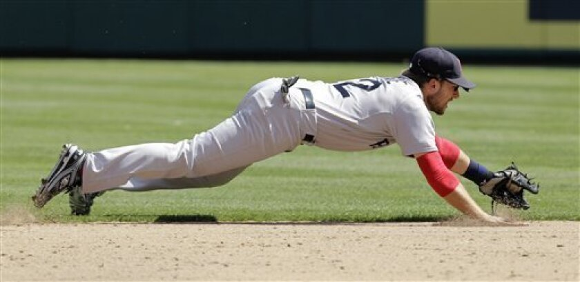 Boston Red Sox shortstop Jed Lowrie grabs a single up the middle by Texas Rangers' Mike Napoli in the seventh inning of an MLB baseball game on Sunday, April 3, 2011, in Arlington, Texas. The Rangers won 5-1. (AP Photo/Tony Gutierrez)