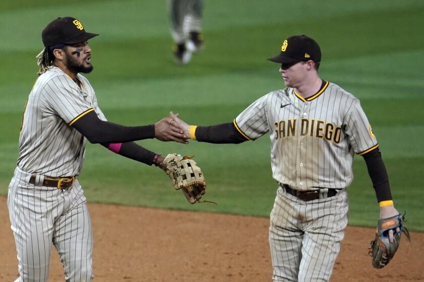 Second baseman Jake Cronenworth, right, shakes hands with shortstop Fernando Tatis Jr.