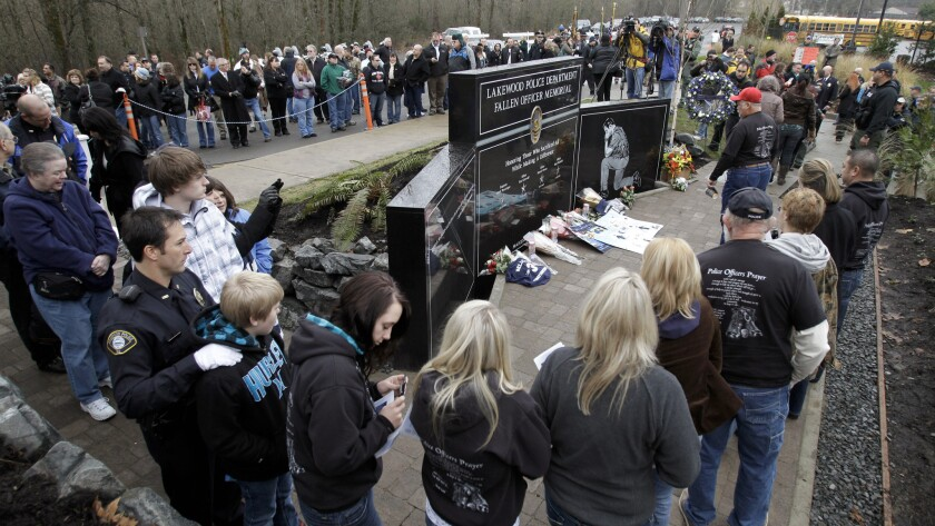 Mourners walk past a memorial for the four slain Lakewood officers at a ceremony marking the first anniversary of their deaths.