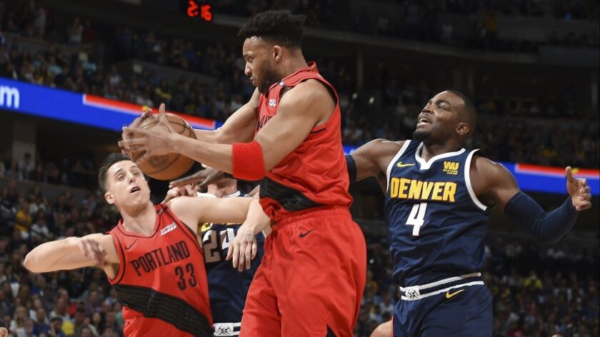 Portland Trail Blazers guard Evan Turner, center, pulls in a rebound in front of Denver Nuggets forward Paul Millsap during Game 7 of the NBA Western Conference semifinals on May 12.