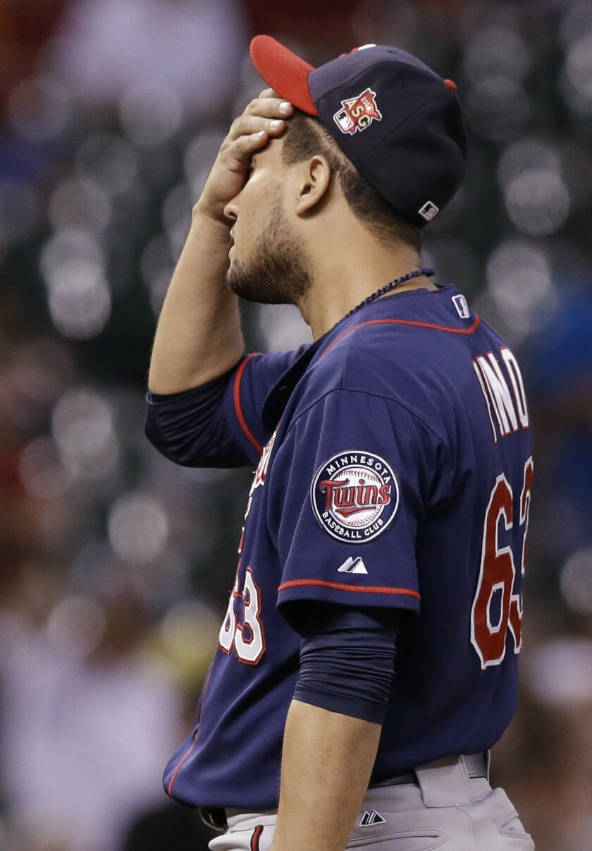 Minnesota Twins starting pitcher Yohan Pino wipes his forehead after giving up a two-run homer to Houston Astros' Chris Carter in the third inning of a baseball game Tuesday, Aug. 12, 2014, in Houston. (AP Photo/Pat Sullivan)