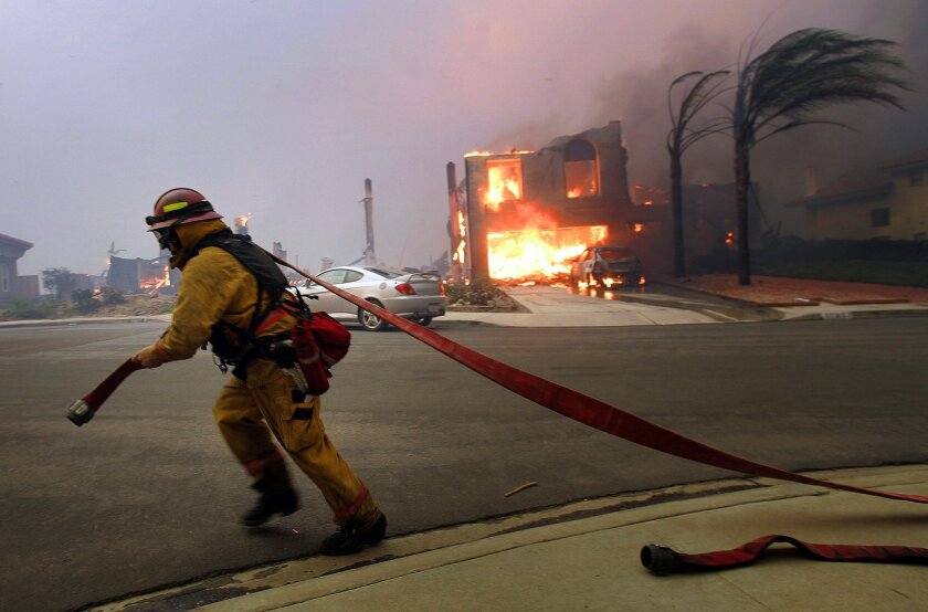 Un bombero trata de controlar el fuego en Rancho Bernardo durante los incendios que afectaron partes del condado de San Diego en octubre del 2007 y que pudieron ser provocados por el equipo y las líneas de corriente de SDG&E.K.C. Alfred/Union-Tribune