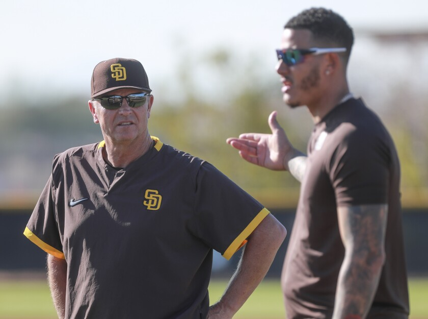 Bench coach Bobby Dickerson listens to Manny Machado at spring training in Peoria, Ariz.