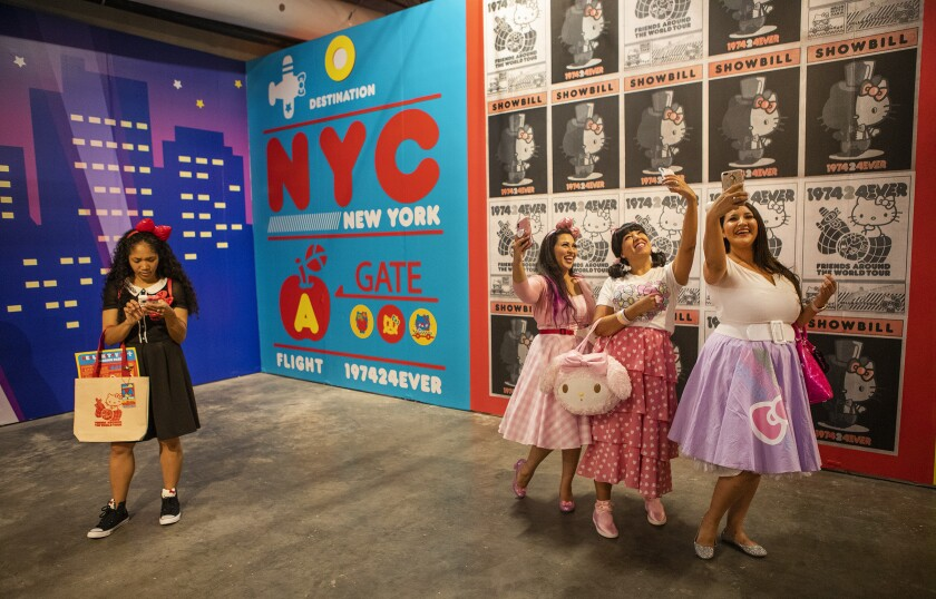 Faheema Chaudhury of Northridge, from left, Jeanne Trejo of Highland Park and Michelle Hernandez of Santa Clarita take selfies inside the New York room at the Hello Kitty Friends Around the World Tour pop-up.