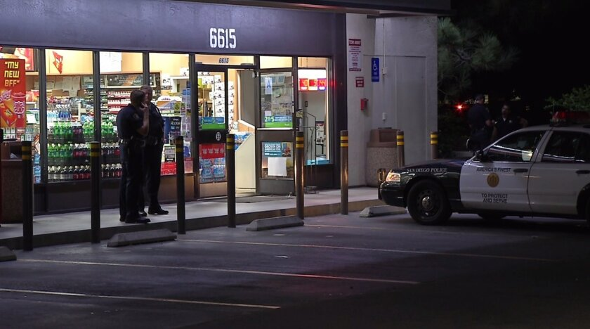 Police officers stand outside a Linda Vista 7-Eleven that was robbed by a man wearing a clown mask and rainbow wig.