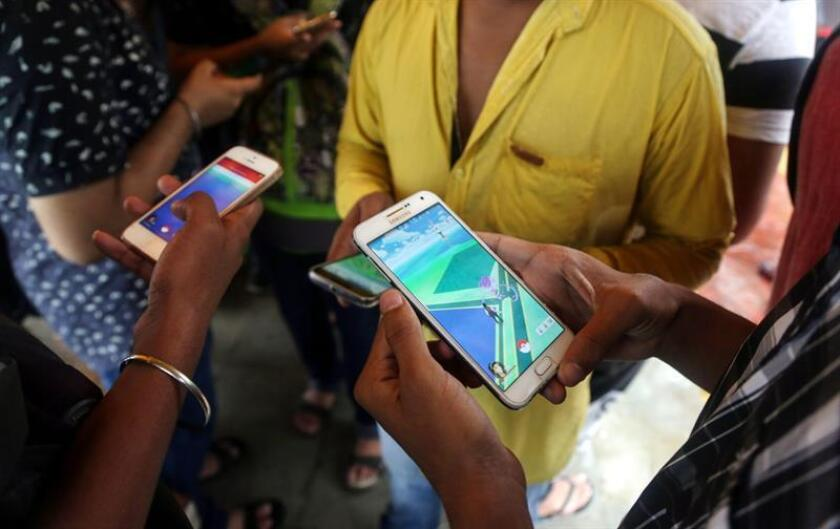 INDIA GAMES POKEMON GO:. Mumbai (India), 31/07/2016.- Indian Pokemon Go game enthusiasts trying to catch a Pokemon character after locating it, during rain shower in Vashi area of New Bombay, on the outskirts of Mumbai, India, 31 July 2016. According to media reports, the launch of Pokemon Go is due in India as the game's developers are trying to find ways to make the server stable to release it. But although the game has not yet been officially launched there, many people have found ways to download the game through the Internet. The game that uses GPS to locate the smartphone's location, has gained a huge popularity among smartphone users and added to the value of Nintendo that partly owns the franchise enterprise that makes Pokemon. EFE/EPA/DIVYAKANT SOLANKI