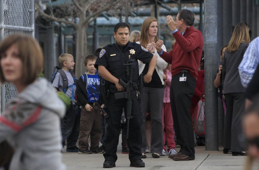 A San Diego police officer guards Kumeyaay Elementary School in Tierrasanta Tuesday as parents pick up their children after a lockdown. The school was locked down after a homicide suspect was spotted in the area. The man was later arrested.