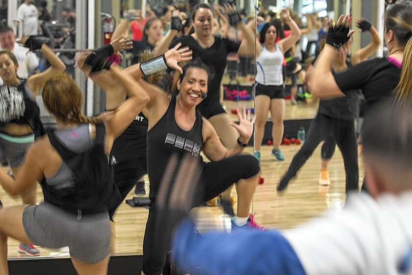 Ann Alperin, center, leads her P90X training class at Fitness 19 in Chino.