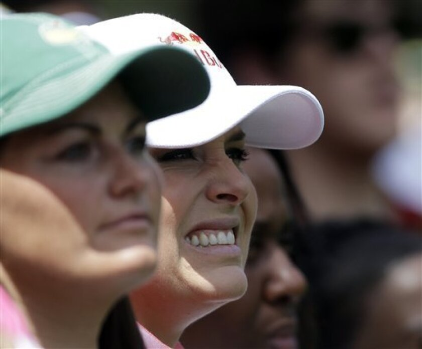 Skier Lindsey Vonn and her physical therapist Lindsay Winninger, left, watch as Tiger Woods tees off on the fourth hole .during the second round of the Masters golf tournament Friday, April 12, 2013, in Augusta, Ga. (AP Photo/David Goldman)