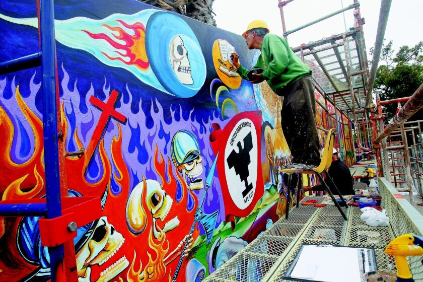 """Salvador """"Sal"""" Barajas works Thursday to restore the """"Historical Mural,"""" which he and other artists painted in Chicano Park in 1973. JOHN GIBBINS • U-T photos"""