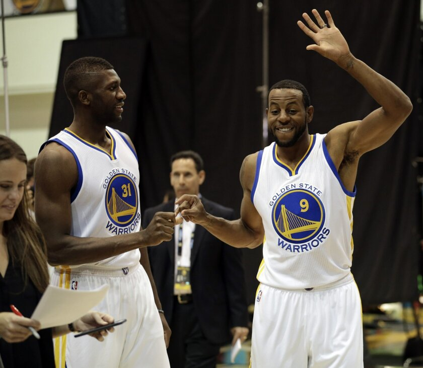 Golden State Warriors' Festus Ezeli, left, and Andre Iguodala (9) greet one another during an NBA basketball media day Monday, Sept. 28, 2015, in Oakland, Calif. (AP Photo/Ben Margot)