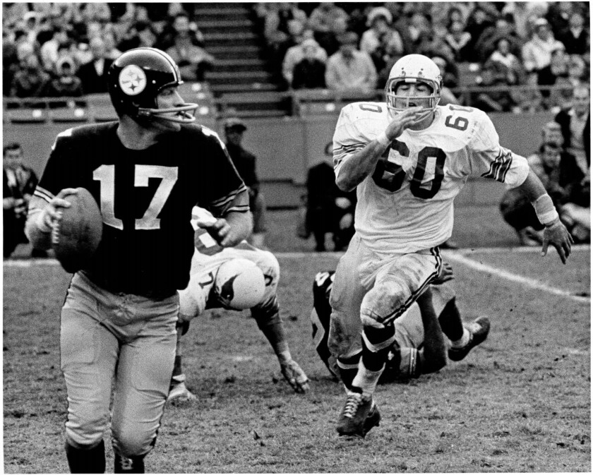 Dave Meggyesy, right, of the St. Louis Cardinals, tries for a sack in an NFL game from the 1960s.