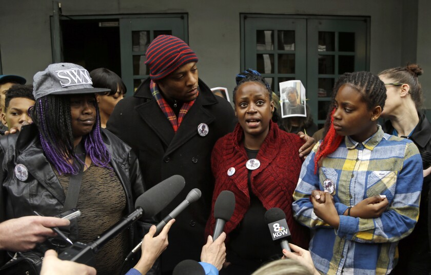 FILE - In this March 22, 2017, file photo, Venus Hayes, second from right, Hayes, the mother the 17-year-old Quanice Hayes, is surrounded by family members as she speaks during a press conference in Portland, Ore. City commissioners apologized Wednesday, March 10, 2021, to the family of a teenager who was shot and killed by Portland police, before approving a $2.1 million settlement of the family's federal wrongful death lawsuit. The Oregonian/OregonLive reports Quanice Hayes' grandmother and two uncles said they remain disturbed that Officer Andrew Hearst still works for the Police Bureau and faced no discipline. (AP Photo/Don Ryan, File)