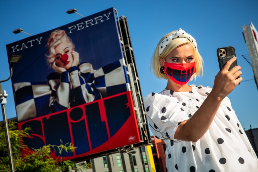 "Katy Perry takes a selfie with a billboard promoting her new album ""Smile,"" near her record label, Capitol Records."