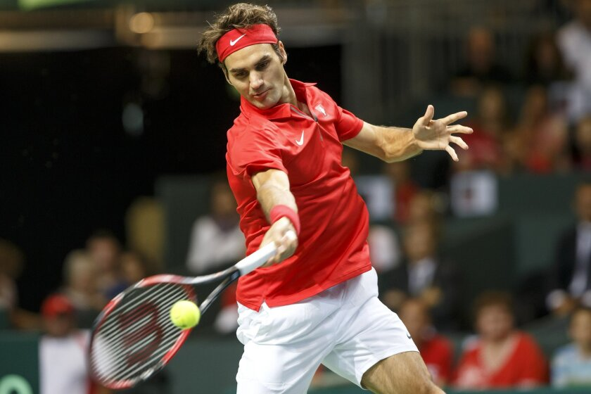 Roger Federer, of Switzerland, returns a ball to Simone Bolelli, of Italy, during the first single match of the tennis Davis Cup World Group semifinal between Switzerland and Italy, in Geneva, Switzerland, Friday, Sept.12, 2014. (AP Photo/Keystone,Salvatore Di Nolfi)