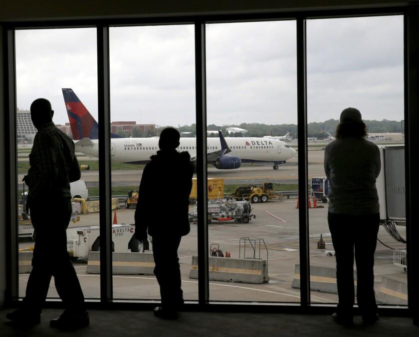 Fotografía de archivo del 14 de abril de 2015 de varios pasajeros de Delta Air Lines observando mientras pasa un avión de esa aerolínea en el aeropuerto internacional Hartsfield de Atlanta. (AP Foto/Charles Rex Arbogast, Archivo)