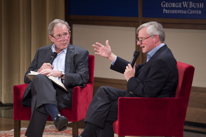 Former President George W. Bush, left, listens to author Jon Meacham talk about his biography of Bush's father, former President George H.W. Bush.