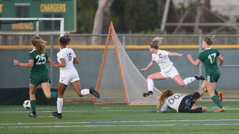 Corona del Mar High's Megan Chelf (12) has to leap over Edison goalie Alyssa Plotkin (00) after shoo