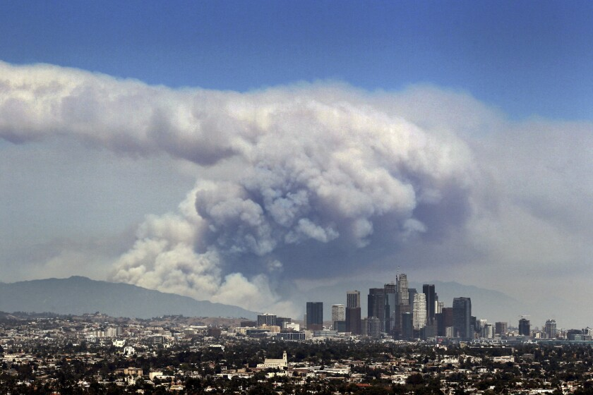 The L.A. skyline and the mountains beyond are shadowed by a huge cloud of smoke from burning wildfires.