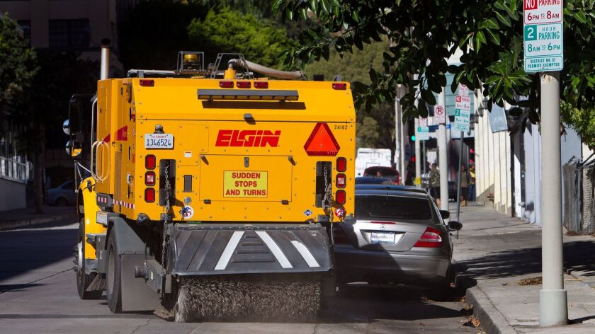 HOLLYWOOD, CA - NOVEMBER 3, 2014: A street sweeper maneuvers around ticketed cars on Monday street