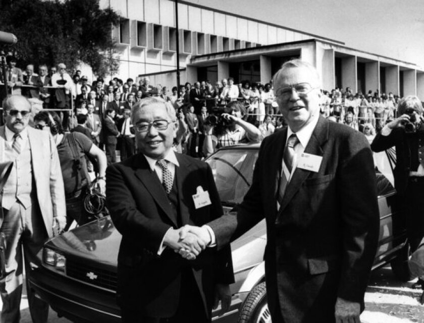 FILE - In this April 13, 1985 file photo, Toyota Motor Corp. Chairman Eiji Toyoda, left, and General Motors Corp. Chairman Roger B. Smith shake hands in front of a Chevrolet Nova as the new United Motor Manufacturing Inc., a $400 million joint venture between GM and Toyota, was inaugurated with a dedication ceremony at the Fremont, Calif., plant. (AP photo/Paul Sakuma, File)