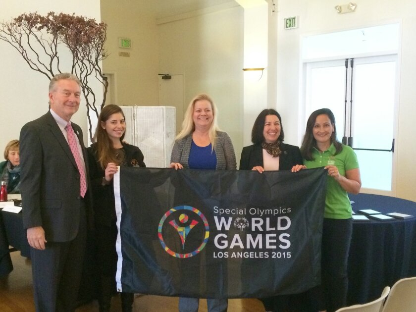 Special Olympics Southern California presents La Jolla Village Merchants Association with the flag of the Special Olympics World Games, July 25-Aug. 2, 2015 in Los Angeles. La Jolla is among the event's Southern California host towns. Pictured are: Special Olympics Southern California CEO Bill Shum