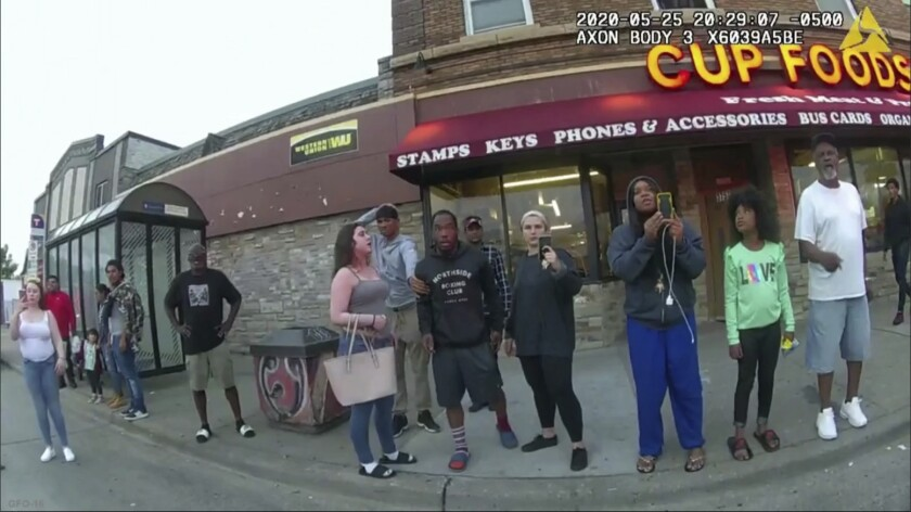Image of bystanders as former police officer Derek Chauvin was recorded pressing his knee on George Floyd's neck .