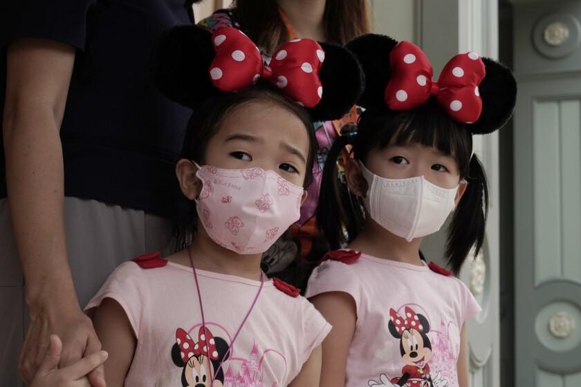 Young visitors wearing face masks look at the iconic cartoon characters Goofy and Pluto at the Hong Kong Disneyland, Friday, Sept. 25, 2020. Hong Kong Disneyland reopened its doors to visitors after closed temporarily due to the coronavirus outbreak. (AP Photo/Kin Cheung)