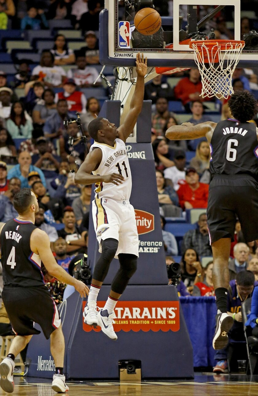New Orleans Pelicans guard Jrue Holiday (11) makes a layup against Los Angeles Clippers guard J.J. Redick (4) and center DeAndre Jordan in the first half of an NBA basketball game in New Orleans, Sunday, March 20, 2016. (AP Photo/Max Becherer)