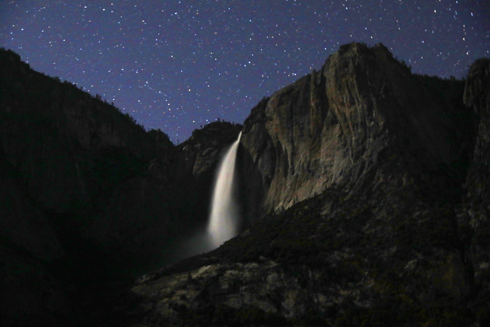 A large waterfall under a starry nighttime sky
