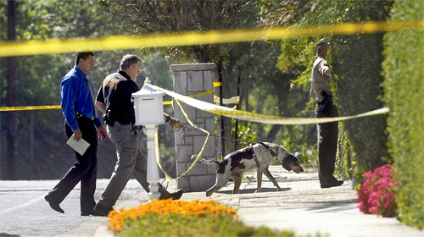 Homicide detectives and a K-9 unit survey the scene in West Covina, Calif., where a woman was found dead.