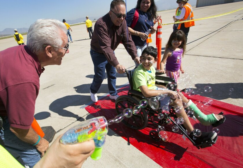 "Omar Mendoza, 11, from the Los Angeles area who has cerebral palsy, gets the red carpet treatment complete with bubbles after finishing his flight during the Challenge Air for Kids and Friends ""Fly Day"" event at Brown Field in Otay Mesa."