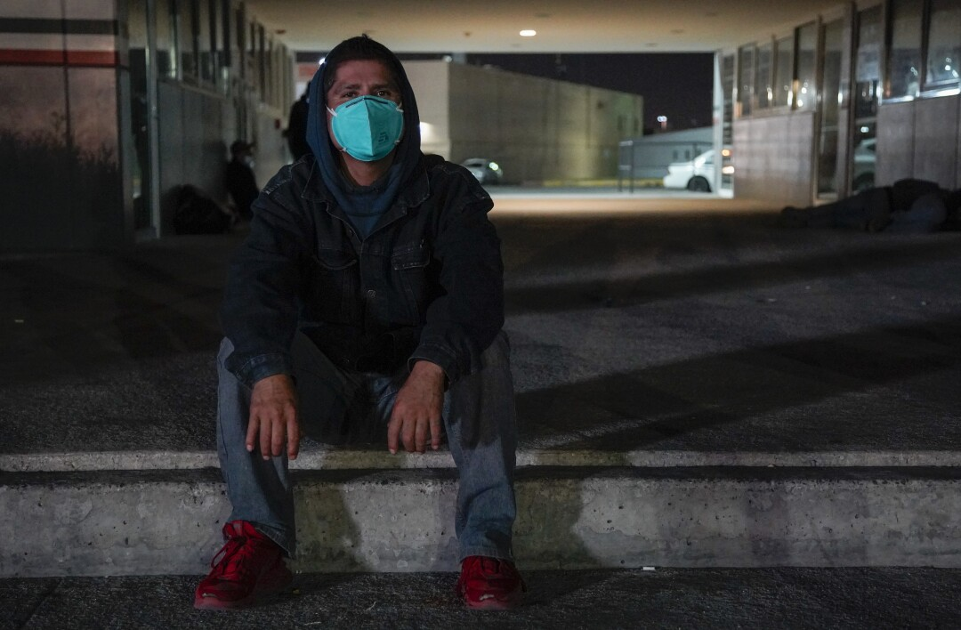 Enrique sits on the sidewalk in a small plaza by the Otay Mesa Port of Entry