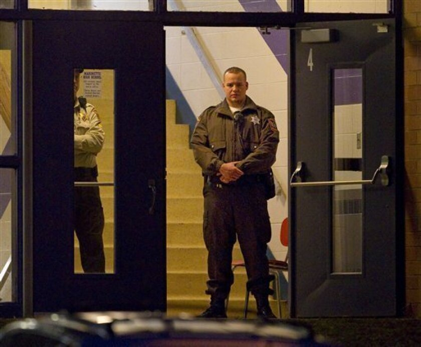 Law enforcement officials stand guard in the doorway of Marinette High School Tuesday morning Nov. 30, 2010 in Marinette, Wis.  Authorities say a teen who held 24 hostages in a Wisconsin classroom has potentially life-threatening injuries from a self-inflicted gunshot wound.  (AP Photo/Mike Roemer)
