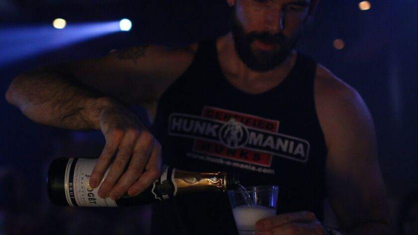 """Hunk-O-Mania male revue performer """"James Thompson,"""" birth name not given, pours champagne for atten"""