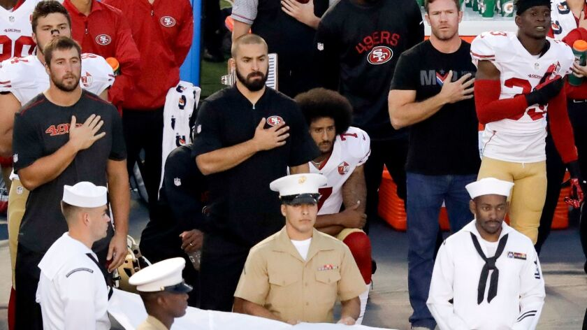 San Francisco 49ers quarterback Colin Kaepernick, middle, sits during the national anthem before the